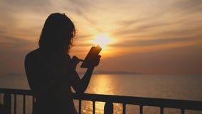 Het meisje gebruikt mobiele telefoon op het schip tijdens zonsondergang op haar vakantie Langzame Motie 1920x1080 stock videobeelden