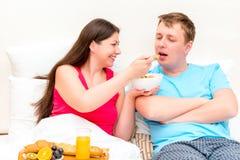 Het meisje geeft aan haar echtgenootmuesli Royalty-vrije Stock Fotografie