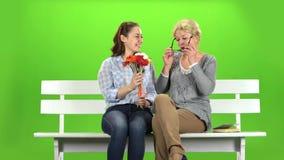 Het meisje geeft bloemen aan haar moeder Het groene scherm stock footage
