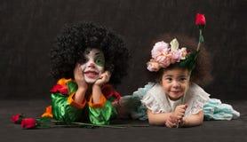 Het meisje geeft bloemen aan jongen - Afrikaanse clown, Royalty-vrije Stock Fotografie