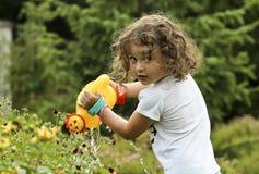 Het meisje geeft de bloemen in de tuin water Royalty-vrije Stock Afbeelding