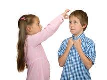 Het meisje geeft flick op het voorhoofd van de jongen, op wit Stock Foto