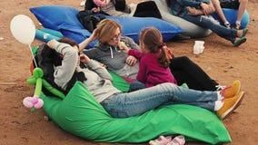 Het meisje geeft pogingsroomijs aan vrouw ligt op beanbags op zand De zomerfestival stock footage