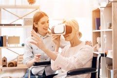 Het meisje geeft thuis voor bejaarde De vrouw gebruikt virtuele werkelijkheid stock afbeeldingen
