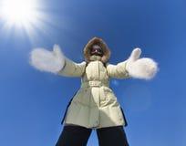Het meisje gekleed in warme kleren rekt uit haar handen aan u uit tegen heldere zon Het omhelzen helpend handen Geklede handen stock fotografie