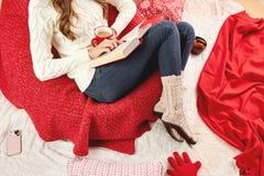 Het meisje gekleed in witte gebreide sweater, jeans en gebreide sokken leest een boek liggend op rood-witte dekens en hoofdkussen stock foto