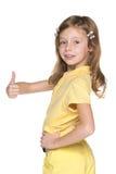 Het meisje in gele blouse houdt haar duim tegen Royalty-vrije Stock Fotografie