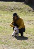 Het meisje geniet op het gras met een wit van weinig hond stock foto