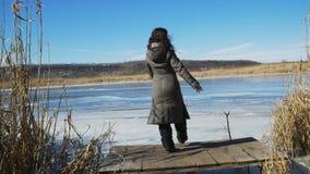 Het meisje geniet van de vrede en schoonheid van aard, van de lopend op een houten pijler op de bank van een bevroren rivier stock video