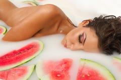 Het meisje geniet van een bad met melk en watermeloen. stock afbeeldingen