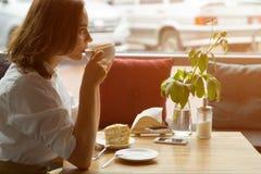 Het meisje geniet van een geurige koffie en van een zoete cakezitting in een koffie Bedrijfsvrouw die tijdens onderbreking rusten Royalty-vrije Stock Foto