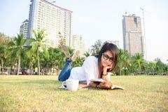 Het meisje geniet van lezend een boek leggend op gras van park royalty-vrije stock afbeelding