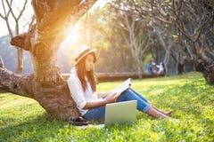 Het meisje geniet van lezend een boek onder de boom stock foto