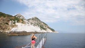 Het meisje geniet van op neus van de boot en het letten van de op reis over het overzees dichtbij eilanden zijn als Titanik-scène stock videobeelden