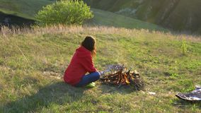 Het meisje geniet van openluchtrecreatie Bradende worsten op de brand Picknick in de avond in aard stock footage