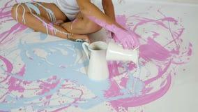 Het meisje giet blauwe verf van een kruik op haar lichaamszitting op een wit canvas stock videobeelden