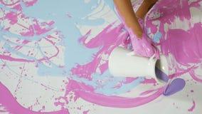 Het meisje giet blauwe verf van een kruik op haar lichaamszitting op een wit canvas stock footage