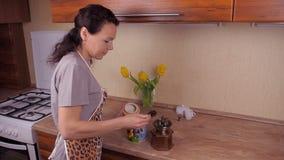 Het meisje giet koffiebonen In de keuken, bidt een vrouw koffiebonen Het meisje in de keuken trekt fartuhe koffiebonen van c stock footage