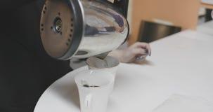 Het meisje giet kokend water van een elektrische ketel in koppen stock videobeelden