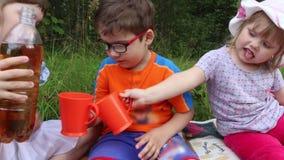 Het meisje giet limonade voor jongen en meisje onder gras stock footage