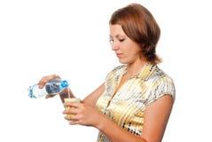 Het meisje giet water in een glas royalty-vrije stock afbeelding