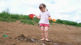 Het meisje giet water van een emmer in het zand Het spelen van het kind op het strand stock videobeelden