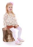 Het meisje ging zitten op een stomp Royalty-vrije Stock Fotografie