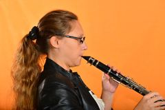 Het meisje in glazen in een zwart jasje speelt de klarinet stock foto's