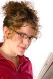 Het meisje in glazen leest tijdschrift Royalty-vrije Stock Afbeeldingen