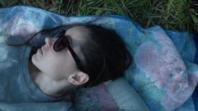 Het meisje in glazen ligt op de draagstoel in het groene gras Het mooie jonge vrouw rusten die op het gebied liggen stock footage