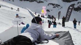 Het meisje in GLB van folie wordt gemaakt ligt met gele luchtballon die Snowboarder het berijden stock footage