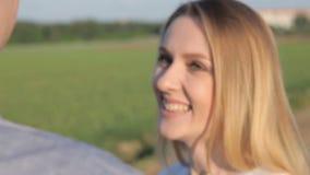 Het meisje glimlacht aan de kerel op de straat stock video