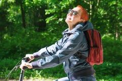 Het meisje glimlacht gelukkig Het berijden in het Park op een Fietspad Gezicht dat aan zonlicht wordt blootgesteld stock fotografie