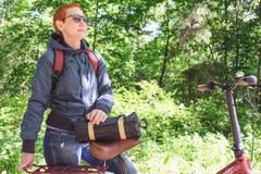 Het meisje glimlacht gelukkig Het berijden in het Park op een Fietspad Gezicht dat aan zonlicht wordt blootgesteld stock afbeelding