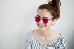 Het meisje glimlacht gelukkig in de roze glazen Een naïeve mening van de wereld in de overgang naar volwassenheid stock foto