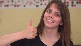 Het meisje glimlacht voor camera en geeft duimen op stock video