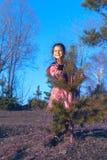 Het meisje gluurt uit van achter de boom Stock Afbeeldingen