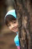 Het meisje gluurt van boom. royalty-vrije stock afbeeldingen