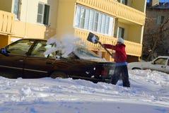 Het meisje graaft auto uit de sneeuw Stock Foto