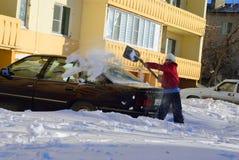 Het meisje graaft auto uit de sneeuw Stock Afbeelding