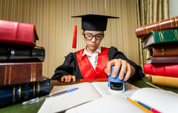 Het meisje in graduatie GLB het spelen in advocaat en het zetten van zegel  stock afbeeldingen