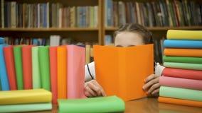 Het meisje in grote glazenhuiden achter een boek, leest een boek stock video