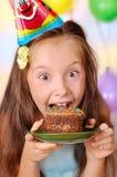 Het meisje in haar verjaardagscake absorbeert Stock Foto's