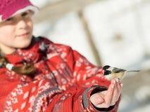 Meisje die een vogel voeden stock foto