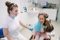 Het meisje heeft een tandpijn De tandarts zal aan de pati?nt helpen royalty-vrije stock afbeelding