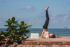 Het meisje heeft een yogapraktijk op de houten vloer met laptop Stock Foto