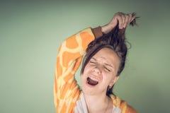 Het meisje heeft haarproblemen Tienervrouw die probleem met verward slonzig haar hebben Het concept van Haircareproblemen Heldere stock foto