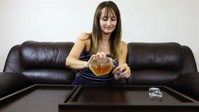 Het meisje heft een glas op en biedt te drinken aan stock video