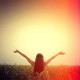 Het meisje heft haar handen aan de hemel op en voelt vrijheid royalty-vrije stock afbeelding