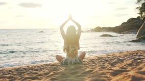 Het meisje heft haar handen op het zitten op het zand door de oceaan op stock videobeelden